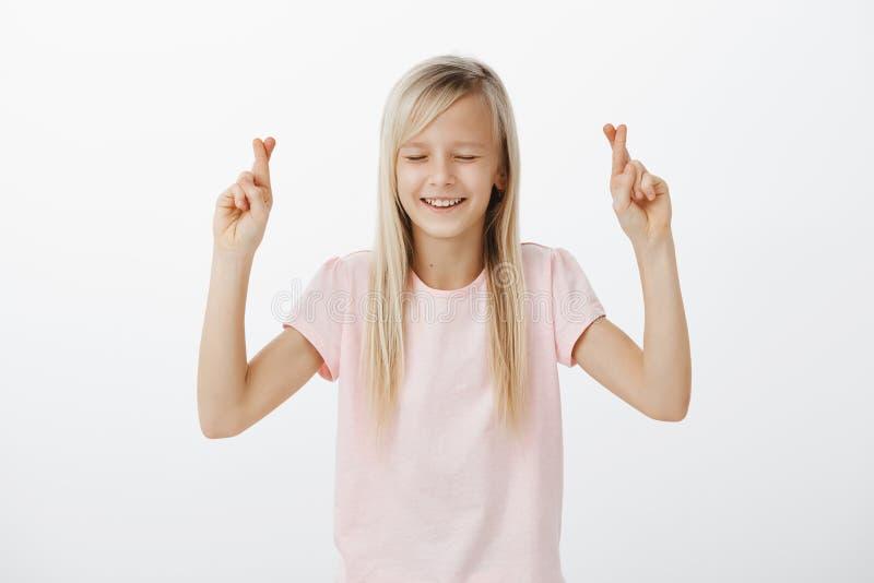 A mamã da esperança compreenderá o que eu quero para o aniversário Menina adorável ansiosa feliz com o cabelo louro, levantando a fotografia de stock