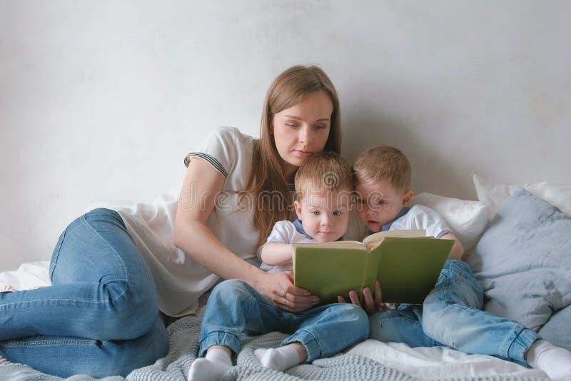 A mamã da família e duas crianças dos irmãos gêmeos leram os livros que colocam na cama Tempo da leitura da família fotos de stock