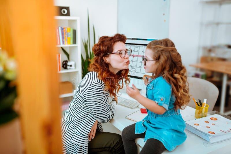 Mamã de amor que beija seu pouco cutie após o trabalho em casa imagens de stock