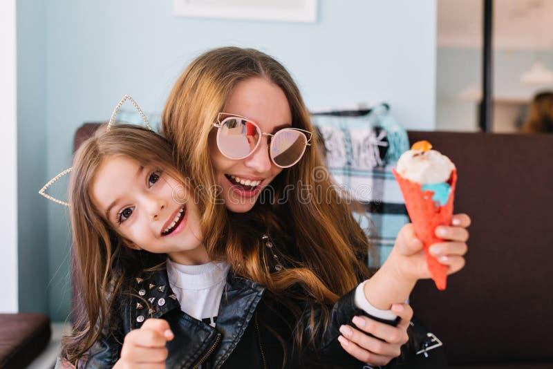 Mamã de riso na moda nos óculos de sol que têm o divertimento com filha entusiasmado dentro Retrato de comer moreno bonito da men foto de stock