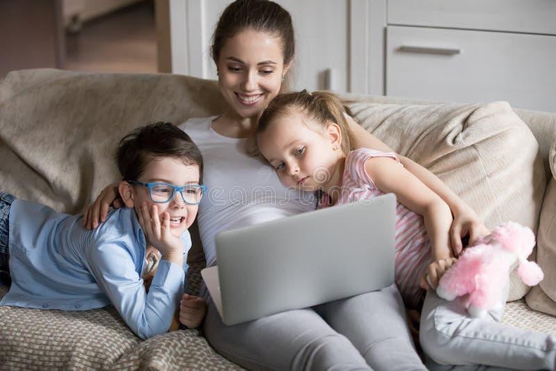 Mamã de sorriso que relaxa com as crianças em desenhos animados de observação do sofá imagem de stock