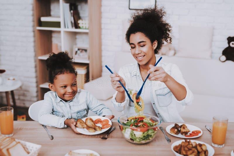 A mamã derrama o alimento para a menina Estúdio e tempo junto fotografia de stock royalty free
