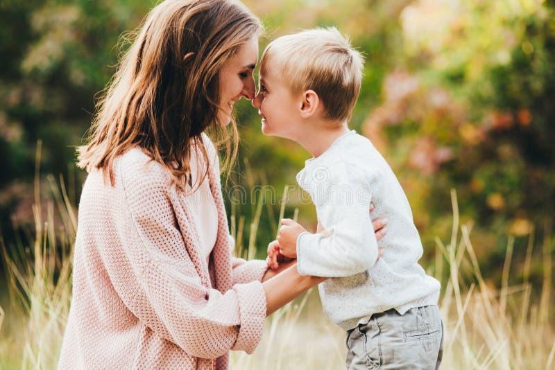 Mamã e abraço e riso do filho no parque do outono Espaço para o texto foto de stock