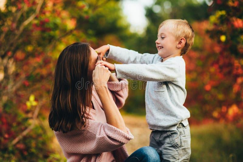 Mamã e abraço e riso do filho no parque do outono Espaço para o texto imagem de stock royalty free