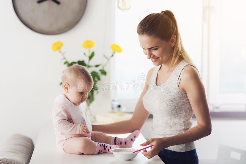 Mamã e bebê na cozinha A mulher está indo alimentar o bebê com comida para bebê imagens de stock royalty free