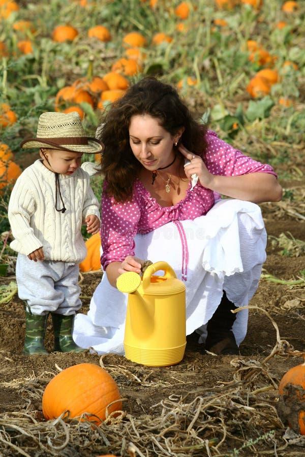 Mamã e criança com lata molhando fotografia de stock