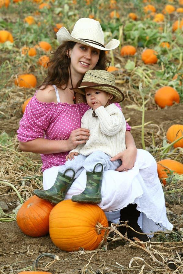 Mamã e criança em uma correcção de programa da abóbora imagens de stock royalty free