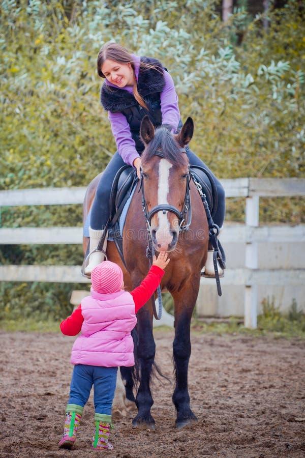 Mamã e criança no cavalo imagens de stock