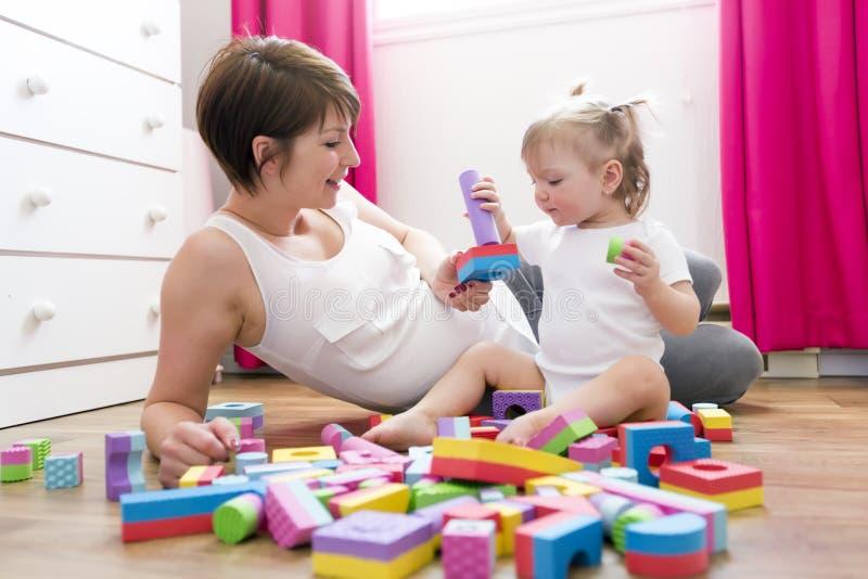 Mamã e criança que jogam brinquedos do bloco em casa fotos de stock