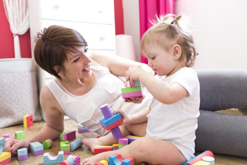 Mamã e criança que jogam brinquedos do bloco em casa fotografia de stock royalty free