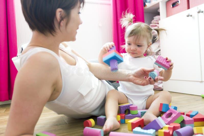 Mamã e criança que jogam brinquedos do bloco em casa imagens de stock royalty free