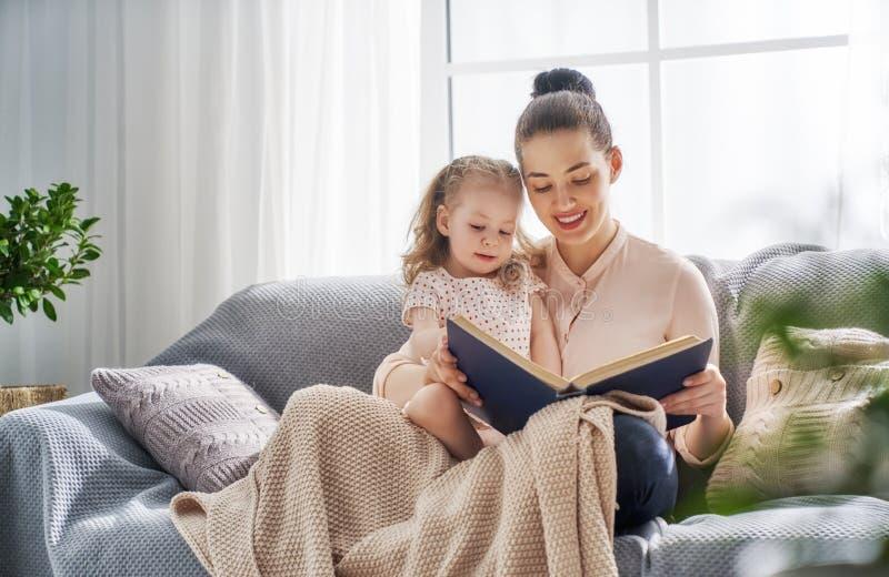 Mamã e criança que leem um livro imagem de stock royalty free