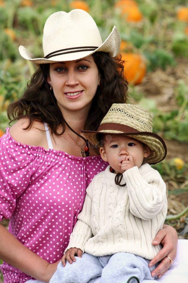 Mamã e criança que sentam-se em uma correcção de programa da abóbora foto de stock