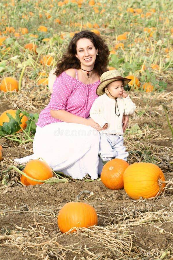 Mamã e criança que sentam-se em uma correcção de programa da abóbora fotografia de stock