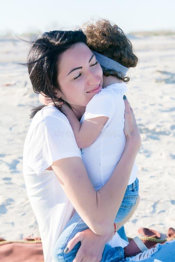 Mamã e doughter na praia, abraçando junto foto de stock royalty free