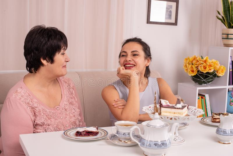 A mamã e a filha adulta estão sentando-se na tabela e no chá bebendo de conversa em casa Relações amigáveis entre diferente imagens de stock