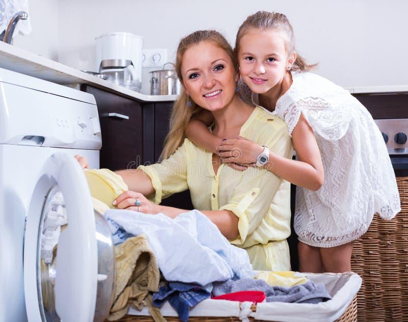 Mamã e filha com o escaninho perto da máquina de lavar foto de stock royalty free