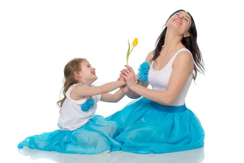 Mamã e filha com uma flor da tulipa imagens de stock royalty free