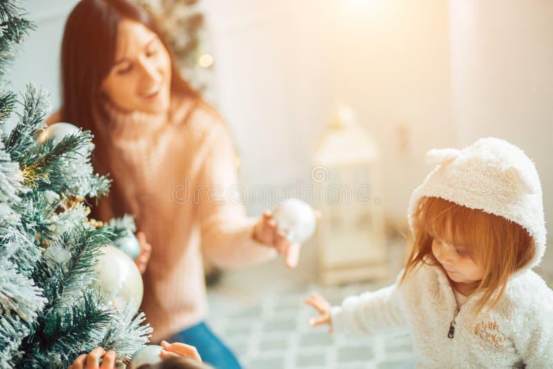 A mamã e a filha decoram a árvore de Natal dentro imagem de stock