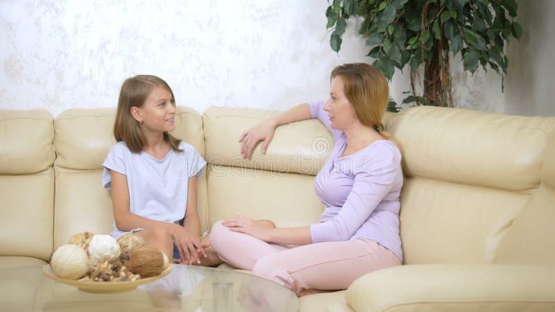Mamã e filha do conceito de uma comunicação a mãe e a filha têm o assento de conversa do divertimento no sofá na sala de visitas imagem de stock