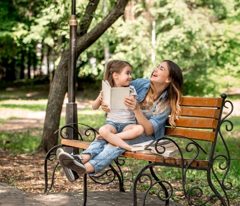 Mamã e filha em um banco que leem um livro imagem de stock