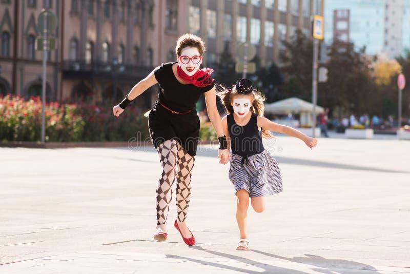 A mamã e a filha estão correndo ao longo da estrada imagens de stock