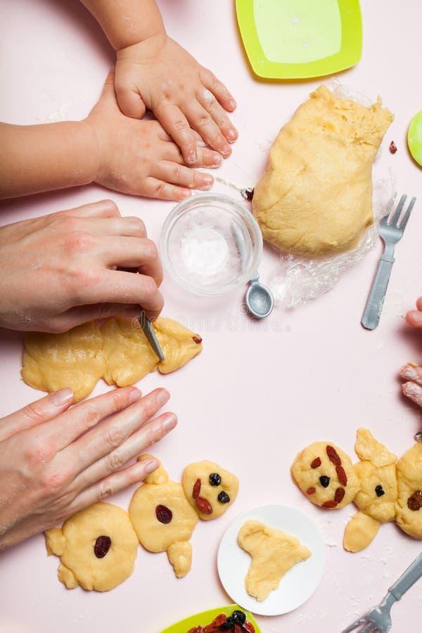 A mamã e a filha estão preparando-se para o Natal, cozinham cookies festivas Árvores dos bonecos de neve e de Natal imagens de stock