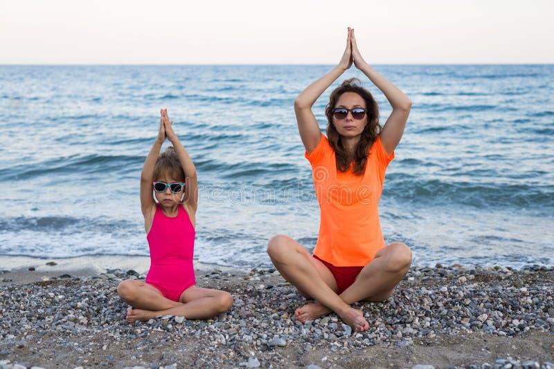 A mamã e a filha meditam sobre a praia, espaço livre fotografia de stock royalty free