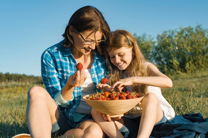 Mamã e filha na natureza, nos feriados do país do verão, na mãe e na criança sentando-se na grama que come morangos imagens de stock