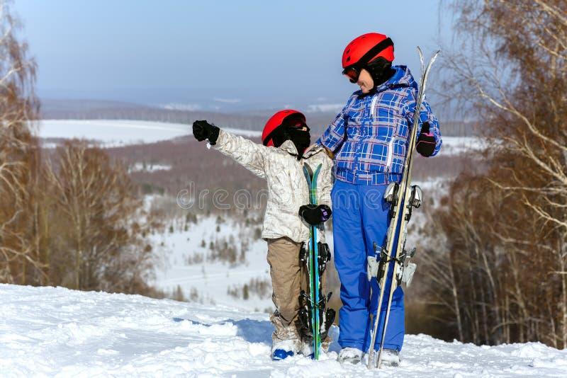 Mamã e filha, no jogo do equipamento do esqui com neve dentro imagem de stock