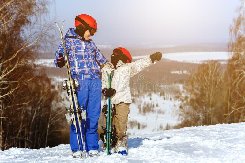 Mamã e filha, no jogo do equipamento do esqui com neve dentro imagens de stock royalty free