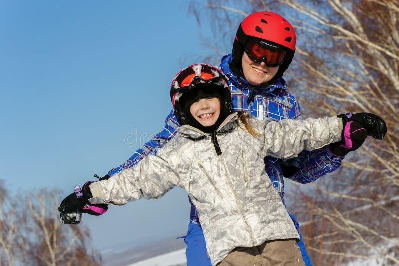 Mamã e filha, no jogo do equipamento do esqui com neve fotografia de stock royalty free