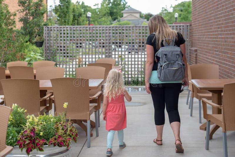 Mamã e filha nova que andam através do café exterior fotos de stock royalty free