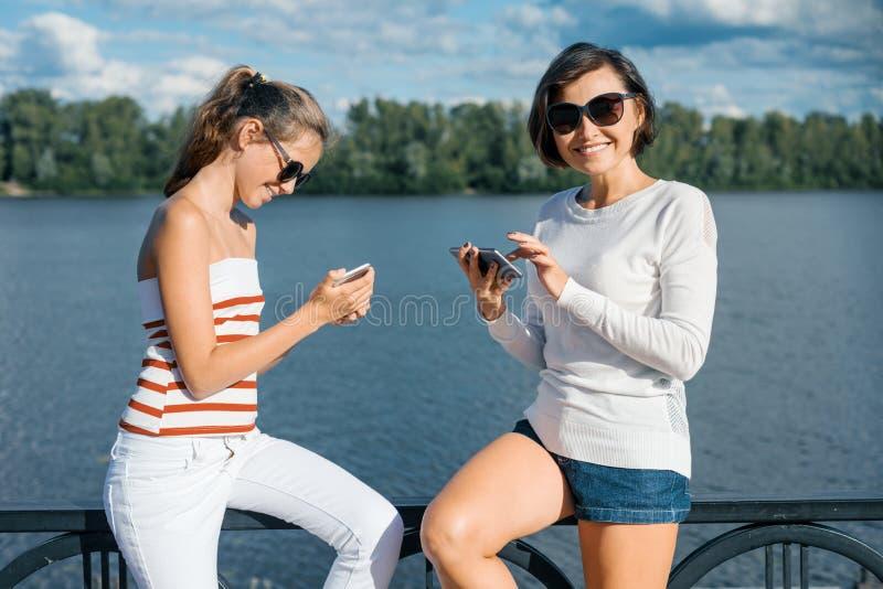 Mamã e filha que andam em um parque do verão perto do rio, usando telefones celulares, fala e sorriso imagem de stock