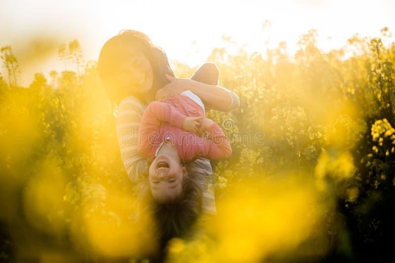 Mamã e filha que apreciam fora, campo da colza Tendo o divertimento junto fotografia de stock