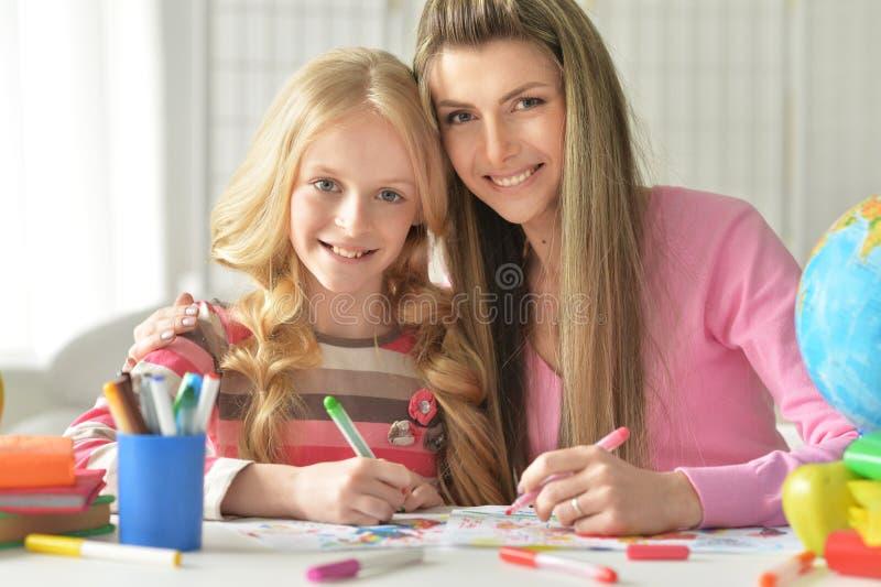 Mamã e filha que fazem lições foto de stock royalty free