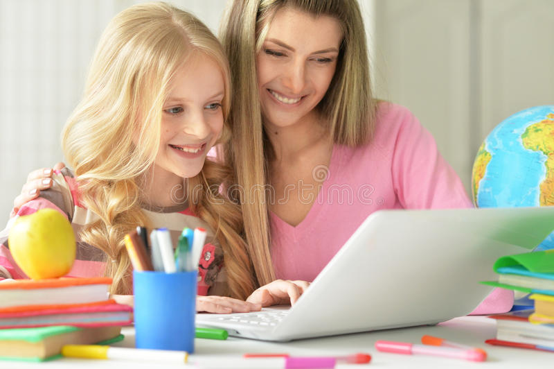 Mamã e filha que fazem lições foto de stock