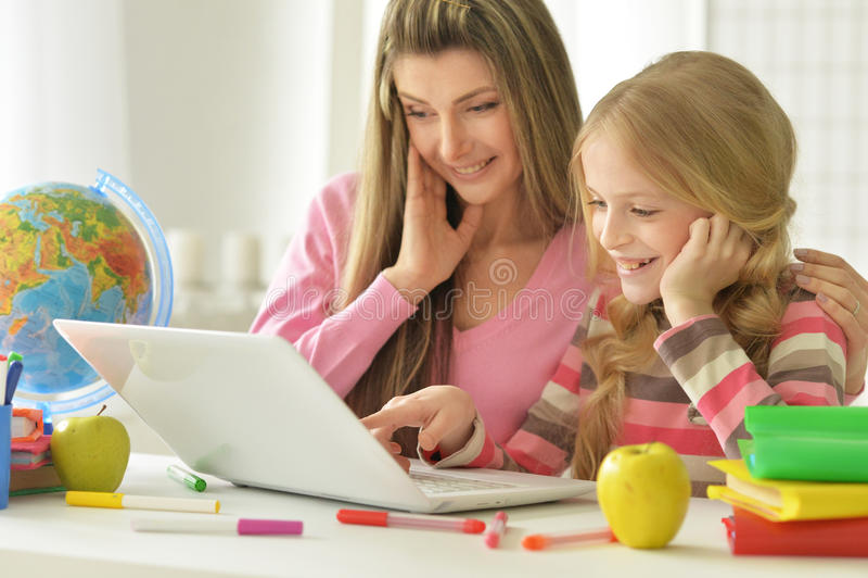 Mamã e filha que fazem lições fotos de stock