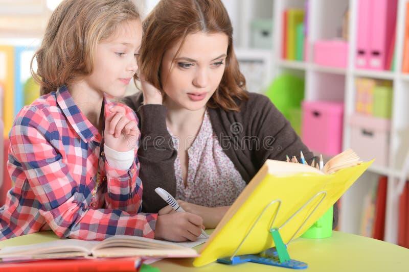 Mamã e filha que fazem lições fotografia de stock