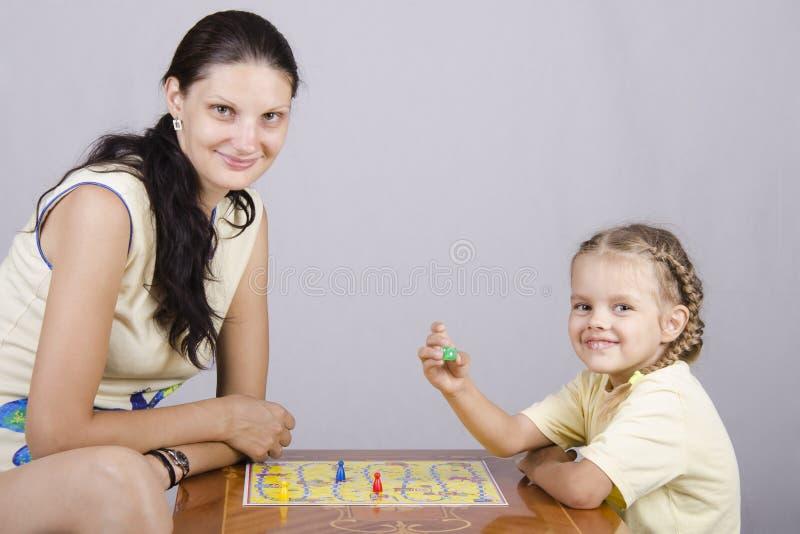 Mamã e filha que jogam um jogo de mesa foto de stock