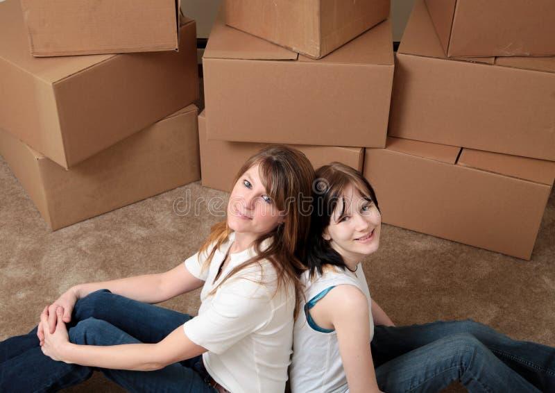 Mamã e filha que movem-se dentro imagens de stock