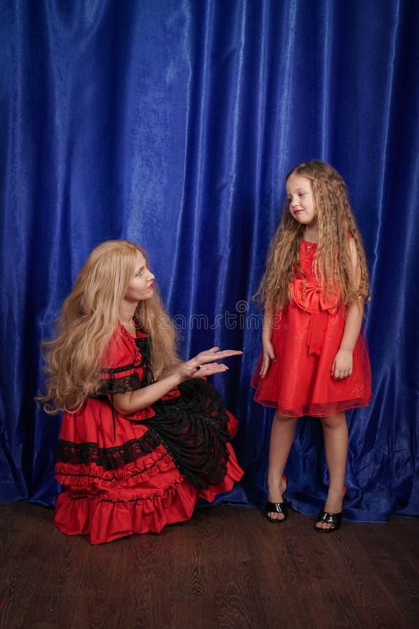 A mamã e a filha são ofendidas e de assentos no assoalho a mamã está tentando estabelecer a paz e a amizade com a criança imagens de stock