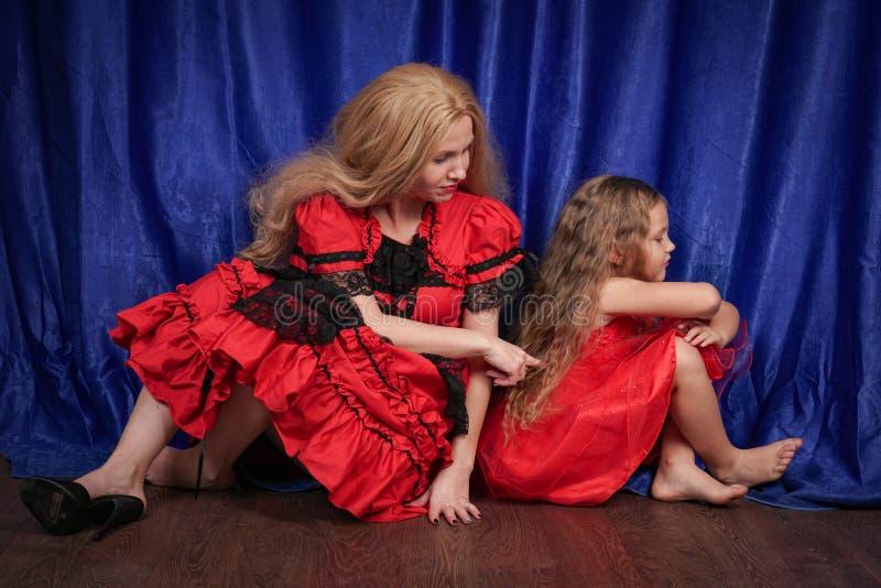 A mamã e a filha são ofendidas e de assentos no assoalho a mamã está tentando estabelecer a paz e a amizade com a criança imagens de stock royalty free