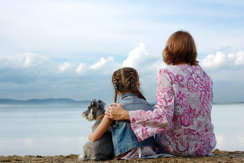 A mamã e a filha sentam o abraço no lago e olham a água fotografia de stock