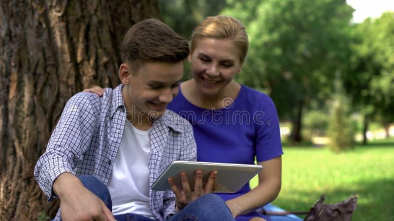 Mamã e filho que olham o vídeo engraçado na tabuleta, rede surfando no parque, tempo junto fotografia de stock