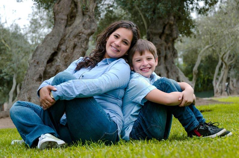 Mamã e filho que sentam-se na grama verde no parque verde Conceito de relações de família felizes fotos de stock