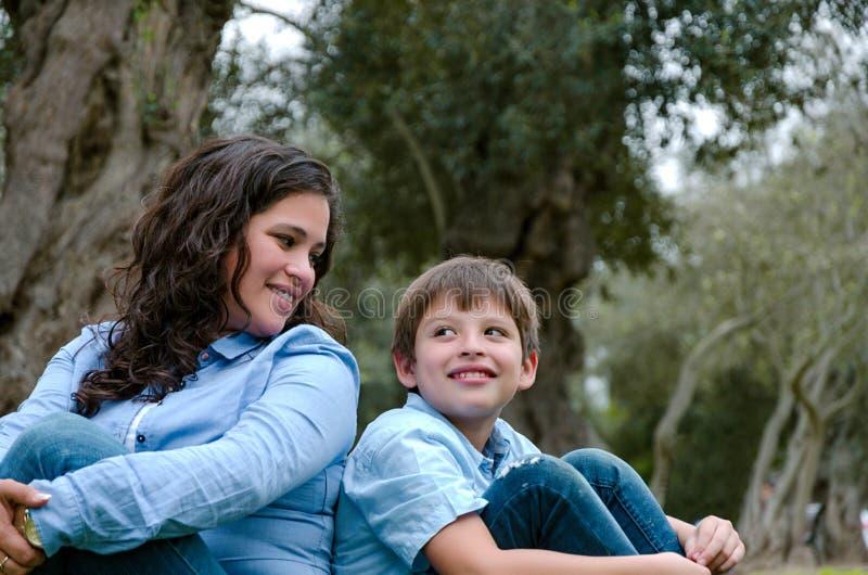 Mamã e filho que sentam-se na grama verde no parque verde Conceito de relações de família felizes foto de stock