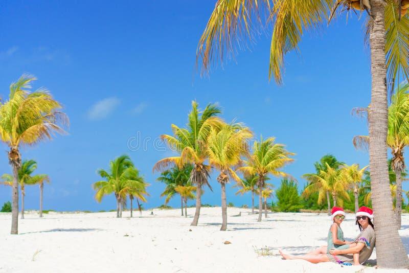 A mamã e a menina novas têm o divertimento na praia tropical no chapéu de Santa que senta-se perto da palmeira fotos de stock royalty free
