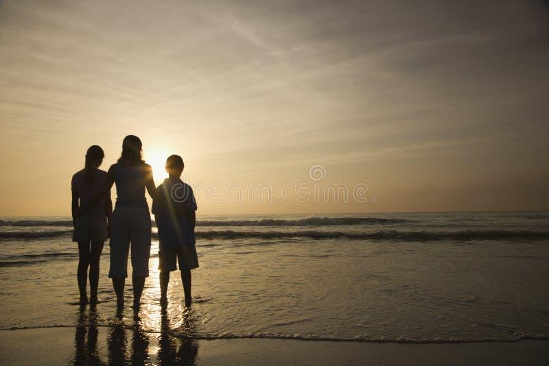 Mamã e miúdos na praia. fotos de stock