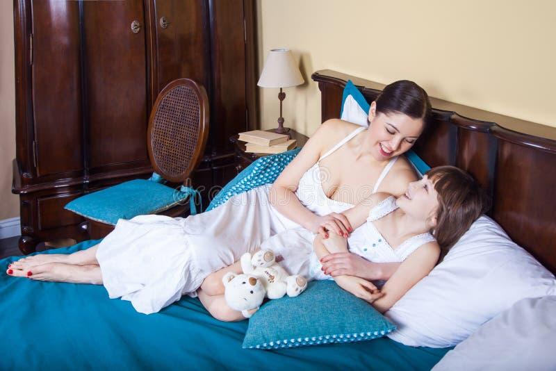 A mamã e a moça encontram-se na cama na manhã, abraçar, sorrindo fotos de stock